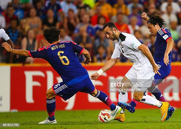 Ali Adnan Kadhim of Iraq fights for the ball with Masato Morishige and Yasuhito Endo of Japan during the first round Asian Cup football match between...