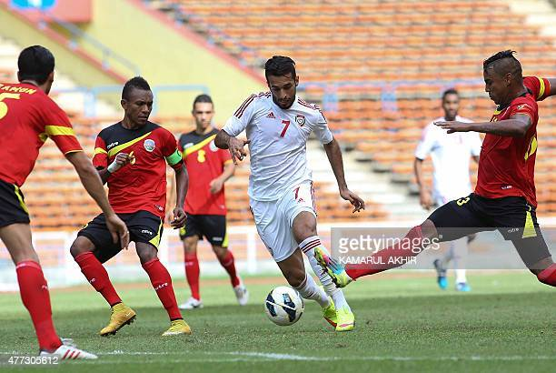 Ali Ahmed Mabkhout of the UAE dribbles the ball East Timor players during the 2018 FIFA World Cup football qualifying match between East Timor and...
