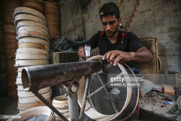 Ali an Iraqi craftsman in his thirties manufactures wooden sieves to be used to filter flour for baking or sand for construction in a workshop in the...