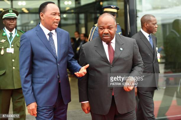 Ali Bongo Ondimba President of Gabon talks with Mahamadou Issoufou President of Niger as they arrive to attend a session of the UN conference on...