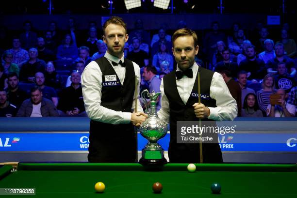 Ali Carter of England and Judd Trump of England shake hands during their final match on day 7 of the 2019 Coral World Grand Prix at The Centaur on...