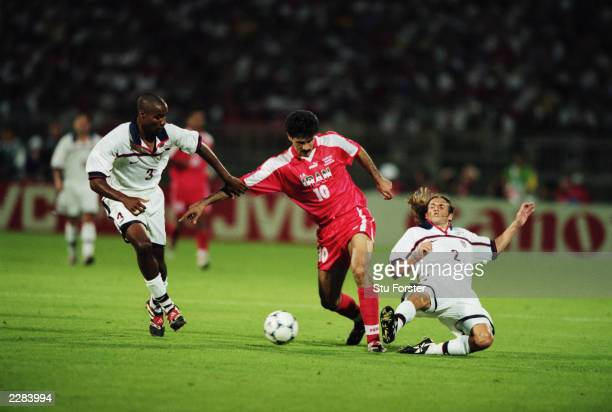 Ali Daei of Iran takes the ball past Eddie Pope and Frankie Hejduk of the USA during the FIFA World Cup Finals 1998 Group F match between the USA and...