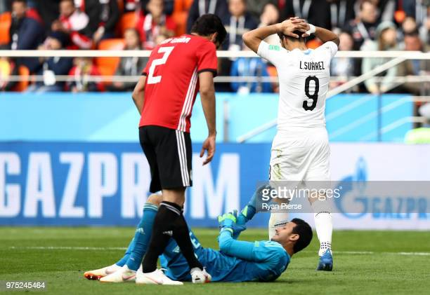 Ali Gabr of Egypt helps up team mate Mohamed Elshenawy as Luis Suarez of Uruguay walks away during the 2018 FIFA World Cup Russia group A match...