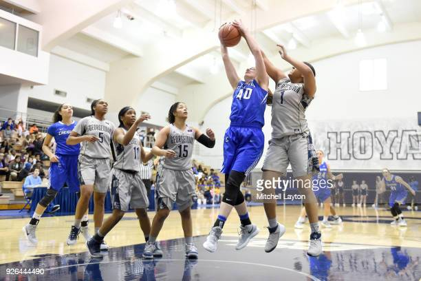Ali Greene of the Creighton Bluejays and Tatiana Thompson of the Georgetown Hoyas fight for a loss ball during a woman's college basketball game at...