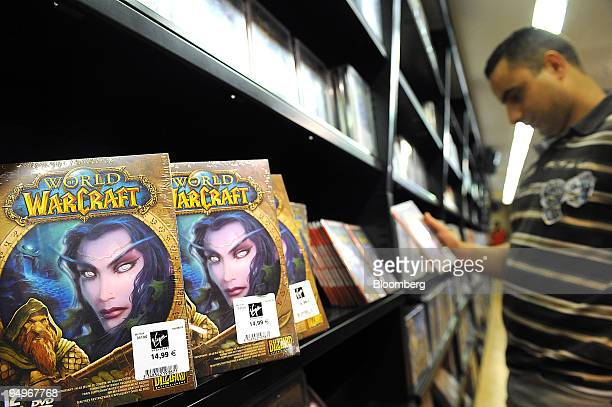 """Ali Guettouche looks at a """"World of Warcraft"""" video game on display at a store in Paris, France, on Tuesday, Sept. 1, 2009. Vivendi SA, owner of the..."""