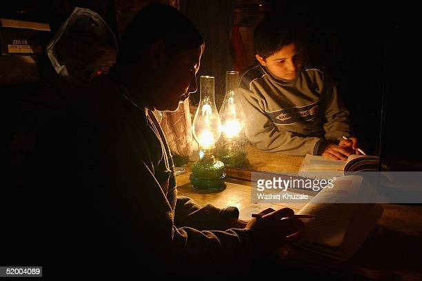 Ali Hussein a 12yearold Iraqi student studies near a mirror with the light of an oil lamp as electricity is off in his neighbourhood January 16 2005...