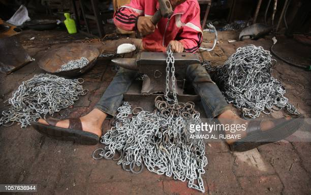 TOPSHOT Ali Jawad who left school to support his family works in an iron chains industry workshop in Haifa street in the capital Baghdad on 5...