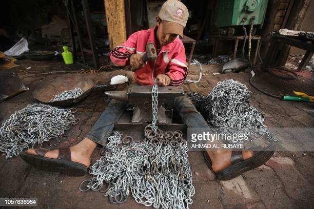 Ali Jawad who left school to support his family works in an iron chains industry workshop in Haifa street in the capital Baghdad on 5 November 2018