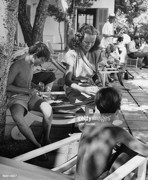 Ali Khan's two son's Karim Aga IV and Amin Khan eating their lunch with Mrs William Woodward Jr