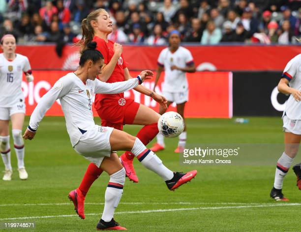 Ali Krieger of the United States kicks the ball away from Janine Beckie of Canada as she takes it down field in the first half of the CONCACAF...