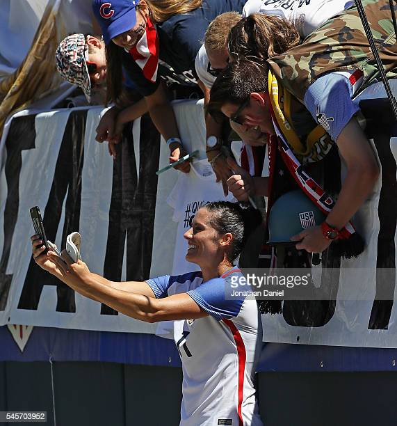 Ali Krieger of the United States poses with fans for a selfie following a win against South Africa after a friendly match at Soldier Field on July 9...