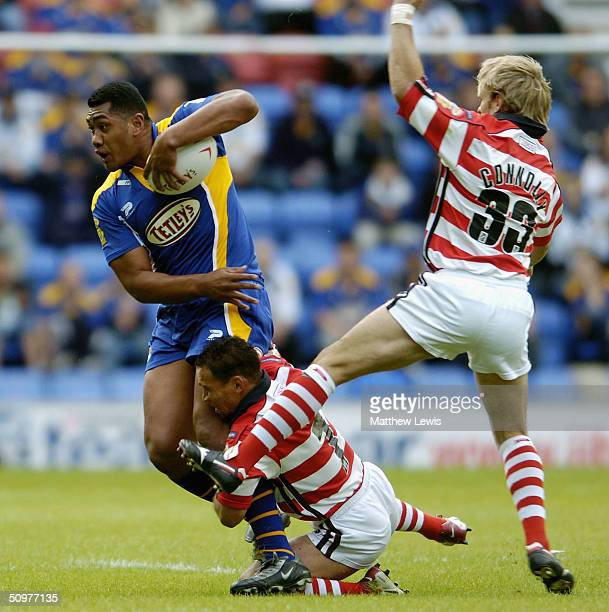 Ali Lauititi of Leeds breaks through the tackles from Adrian Lam and Gary Connolly of Wigan during the Super League match between Wigan Warriors and...