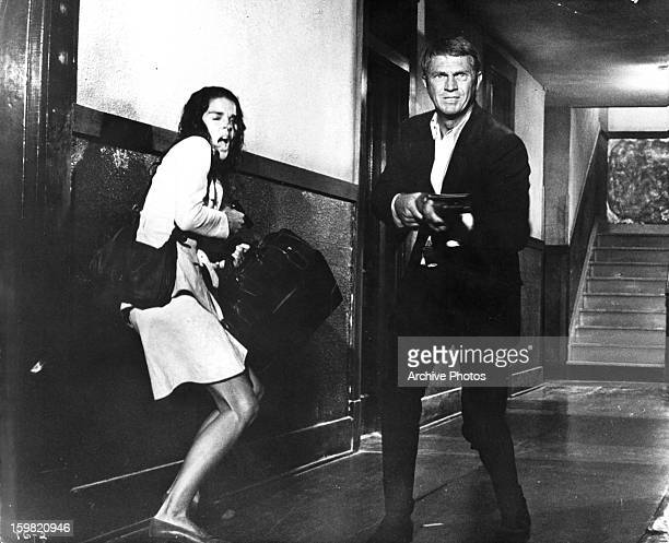 Ali MacGraw recoils as Steve McQueen aims his shotgun in hallway in a scene from the film 'The Getaway' 1972
