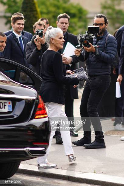 Ali MacGraw wears a black top a black Chanel bag white pants silver flat shoes outside the Chanel Cruise Collection 2020 At Grand Palais on May 03...