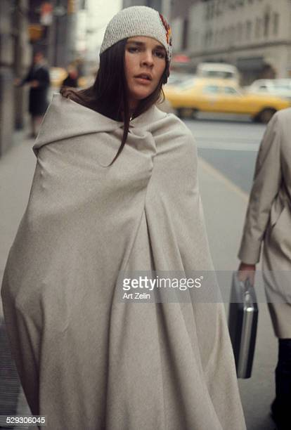 Ali MacGraw wrapped in a blanket walking on the street; circa 1970; New York.