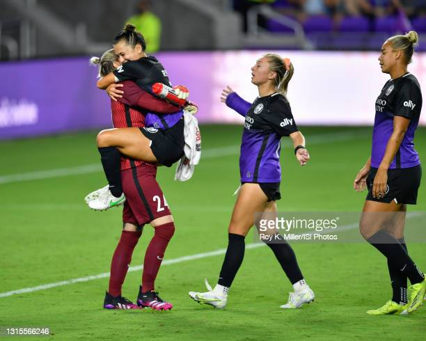 Ali Riley of the Orlando Pride leaps into the arms of Ashlyn Harris of the Orlando Pride to celebrate a victory as Courtney Petersen and Toni...