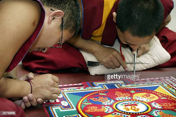 Ali Rinpoche and Lobzang Tuskhor Tibetan monks from the Lhunpo Monastery in southern India help create a sand Mandela one piece of sand at a time at...