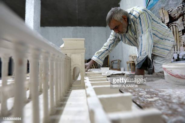 Ali Saleh, a 58-year-old displaced Syrian originally from Palmyra, builds from memory a wood and gypsum model of a prominent archaeological landmark...