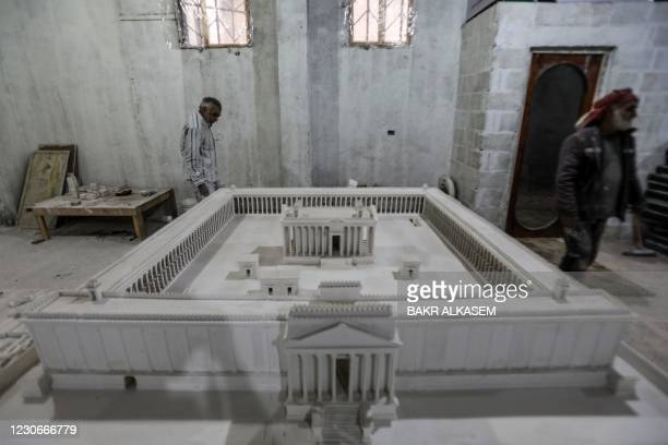 Ali Saleh , a 58-year-old displaced Syrian originally from Palmyra, builds from memory a wood and gypsum model of a prominent archaeological landmark...