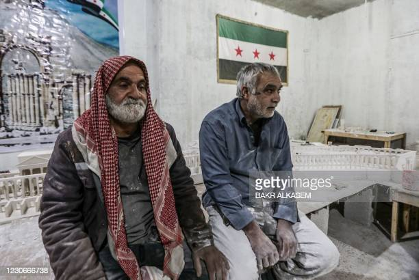 Ali Saleh , a 58-year-old displaced Syrian originally from Palmyra, looks on at the workshop where he builds from memory wood and gypsum models of...