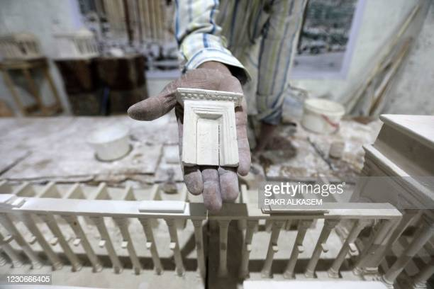 Ali Saleh, a 58-year-old displaced Syrian originally from Palmyra, shows off a model of a gate as he builds from memory a wood and gypsum model of a...