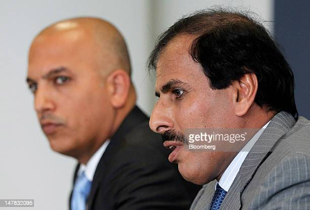 Ali Shareef Al Emadi group chief executive officer of Qatar National Bank SAQ left listens as Sheikh Abdullah Saud Al Thani governor of Qatar's...