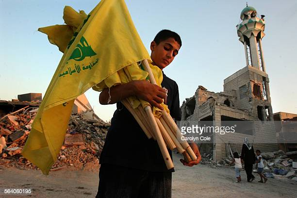 QANA LEBANON – Ali Tiba age 11 holds Hezbollah flags that are going up around the town of Qana in preparation for the burial of over 50 people who...