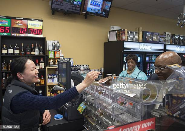 Ali Tsedev sells Powerball lottery tickets at a convenience store in Washington DC January 7 2016 Lottery officials predict Saturday's jackpot will...