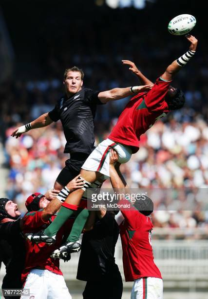 Ali Williams of New Zealand and Goncalo Uva of Portugal stretch for the ball during match fourteen of the Rugby World Cup 2007 between New Zealand...