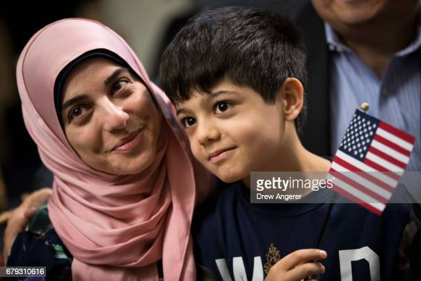 Ali Younes an 8 yearold from Lebanon sits with his mother after becoming a US citizen during a citizenship ceremony at The Bronx Zoo May 5 2017 in...
