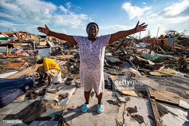 "Aliana Alexis of Haiti stands on the concrete slab of what is left of her home after destruction from Hurricane Dorian in an area called ""The Mud"" at..."