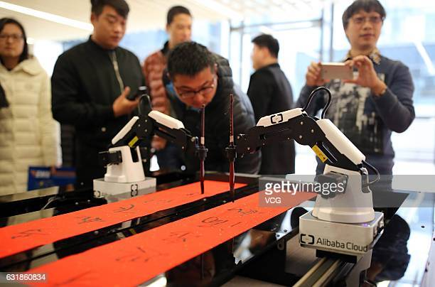 Alibaba employees watch an artificial intelligence robot named ET writing Spring Festival couplets at Alibaba's Xixi District on January 16 2017 in...