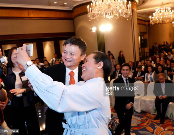 Alibaba Group cofounder and executive chairman Jack Ma poses with a Filipino guest during a news conference on June 25 2018 in Hong Kong China...