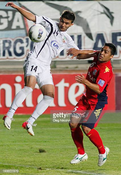 Alibobo Rakhmatullaev of Bunyodkor and Cassio Oliveira of Adelaide compete for the ball during the AFC Champions League quarterfinal second leg match...