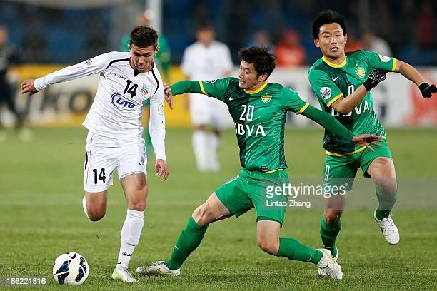 Alibobo Rakhmatullaev of Bunyodkor challenges Zhang Xinxin of Beijing Guoan during the AFC Champions League Group match between Bunyodkor and Beijing...