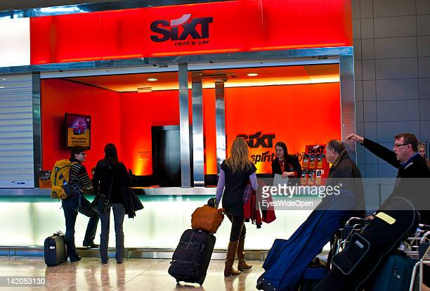 Alicante Airport arrival hall with passengers luggage on trolleys and a Sixt rental car station on February 18 2012 in Alicante Spain