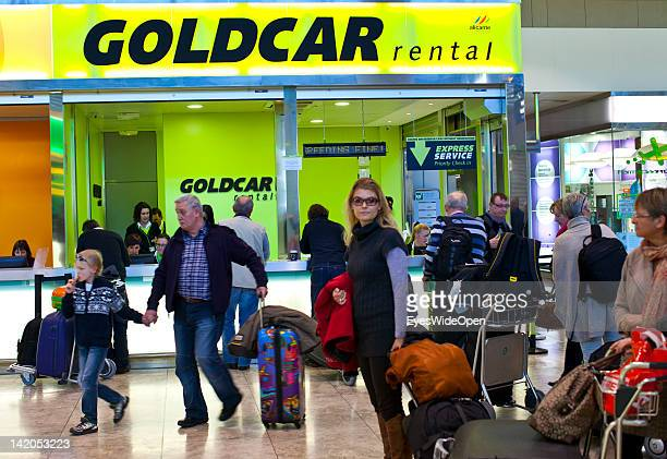 Alicante Airport arrival hall with passengers luggage on trolleys and a Goldcar rental car station on February 18 2012 in Alicante Spain