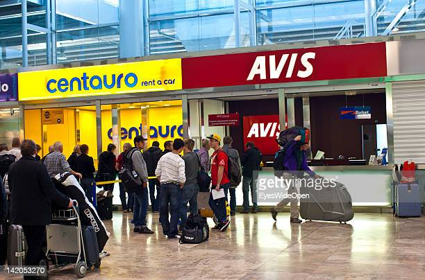 Alicante Airport arrival hall with passengers luggage on trolleys and a Centauro and a Avis rental car station on February 18 2012 in Alicante Spain