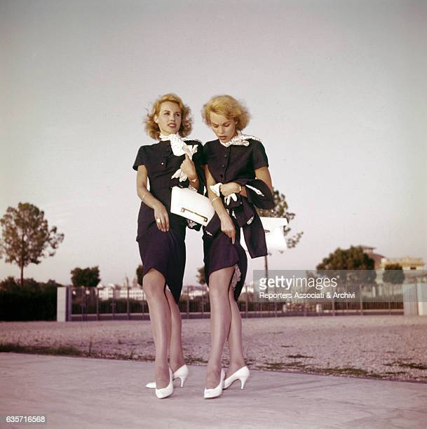 Alice and Ellen Kessler twin sisters and German artistic duo captured while lifting gracefully their dresses up exposing legs Launched by the Italian...