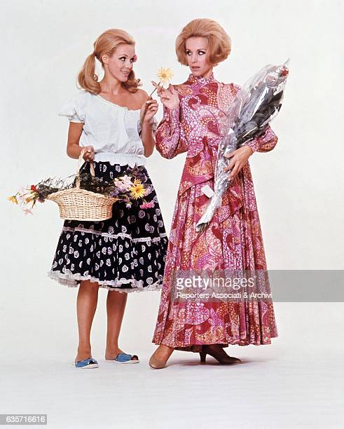 Alice and Ellen Kessler twin sisters and German artistic duo posing in the studio for a photo shoot In the picture a Kessler holds a basket with...
