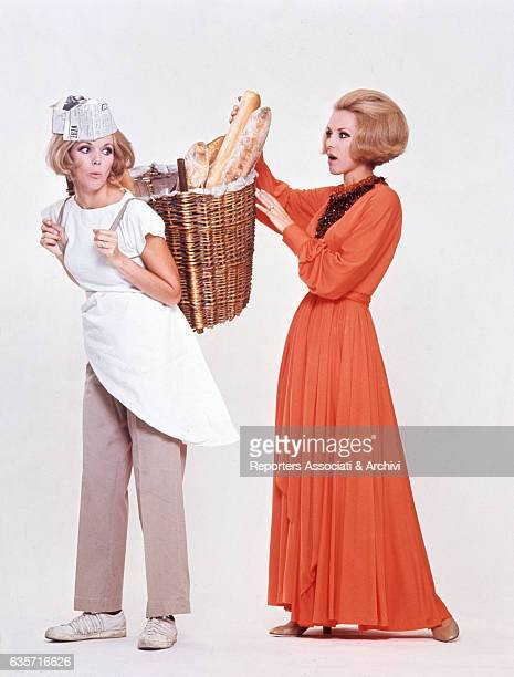 Alice and Ellen Kessler twin sisters and German artistic duo posing for a photo shoot In the picture a Kessler disguised as a baker lets the other...