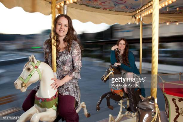 Alice and Irene Fornaciari daughters of the italian singer Zucchero smiling sitting on a carousel Sarzana March 10 2011
