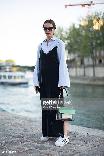 Alice Barbier poses wearing an H and M studio dress Lancel bag and Adidas shoes before the Paul and Joe show at Les Nautes during Paris Fashion Week...