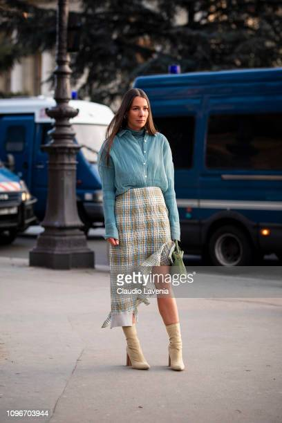 Alice Barbier wearing a light blue shirt checked midi skirt beige ankle boots and green bag is seen in the streets of Paris before the Sacai show on...