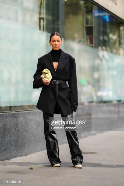 Alice Barbier wears a black turtleneck top with a keyhole, a black oversized blazer jacket, a leather belt, a pale yellow leather bag, black leather...