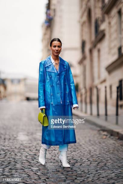 Alice Barbier wears a blue clear trenchc oat white pants white shoes a neon yellow bag outside Altuzarra during Paris Fashion Week Womenswear...