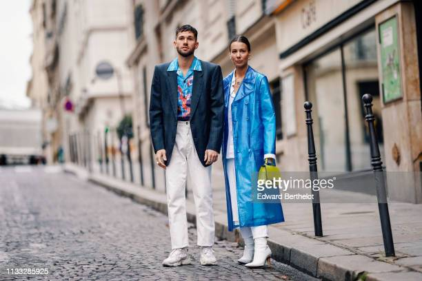 Alice Barbier wears a blue clear trenchc oat white pants white shoes a neon yellow bag JeanSebastien Rocques wears a blazer jacket a floral print...