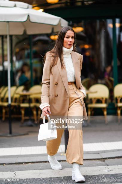 Alice Barbier wears a brown blazer jacket a white turtleneck flare pants white shoes during Paris Fashion Week Womenswear Fall/Winter 2018/2019 on...