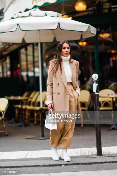 Alice Barbier wears a brown blazer jacket a white turtleneck flare pants white shoes during Paris Fashion Week Womenswear Fall/Winter 2018/2019 on...