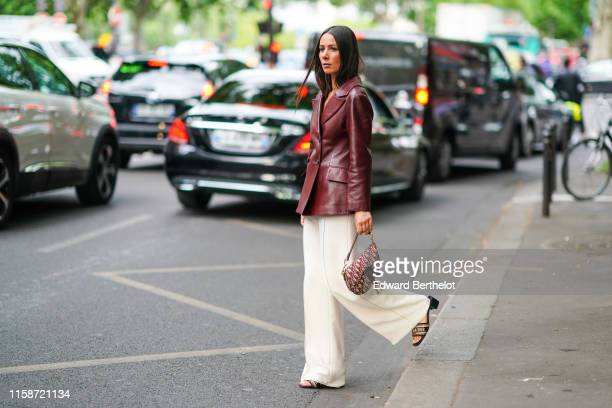 Alice Barbier wears a brown leather doublebreasted jacket white flare pants Christian Dior sandals a Christian Dior monogram saddle bag outside Dior...